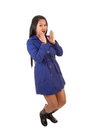 A pretty young Asian woman in a blue coat and boots standing surprised in surprised in the studio for white background. photo