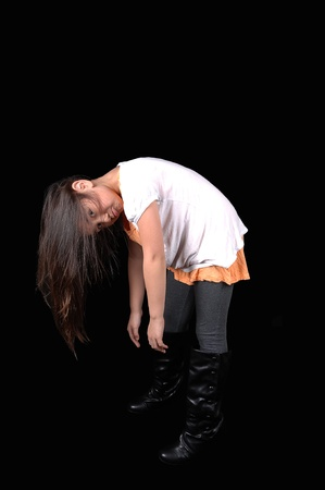 bending down: A young girl in tights and a pink dress and boots holding her head down her long hair falls down, for black background. Stock Photo