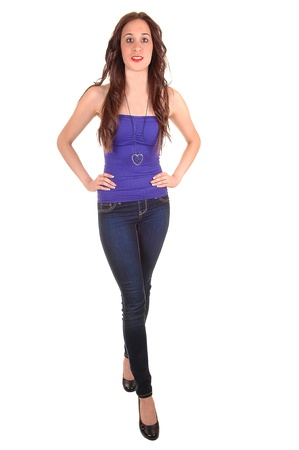 A pretty young woman in jeans and high heels, with a strapless top and  long hair standing in the studio for white background.
