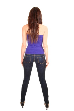 A pretty young woman in jeans and a strapless top standing from  the back in the studio for white background.