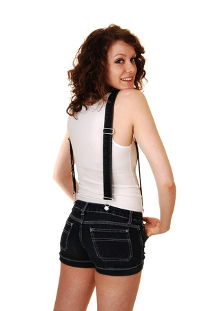 suspender: A young pretty woman in jeans shorts with suspender and a white t-shirt standing from the back, looking over her shoulder, for white background.  Stock Photo