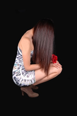 A beautiful young woman in a short tight dress, hocking on the floor in profile in the studio with a rose in her hand, for black background. photo