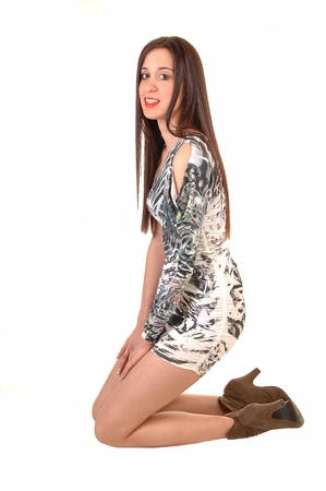 A young pretty woman kneeling in a short tight black and white dress  in the studio, with her long brown hair, for white background.