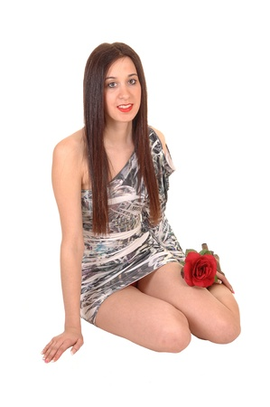 tight dress: A young pretty woman sitting in a short tight gray and white dress in the studio on the floor, with her long brown hair, for white background. Stock Photo