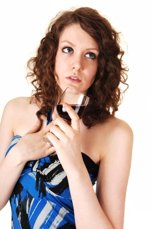 A pretty young woman holding a glass of red wine in her hands,  with her blue eyes, on white background. photo