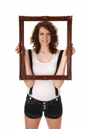 A young pretty woman in jeans shorts with suspender and a white t-shirt standing in the studio holding up a picture frame, for white background. Фото со стока