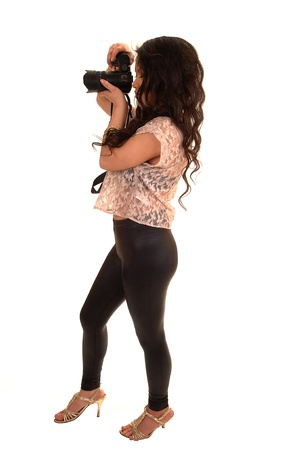 Jonge vrij Aziatische vrouw die beelden met haar camera, in zwarte legging en beige blouse neemt, die zich in de studio voor witte achtergrond bevinden. Stockfoto