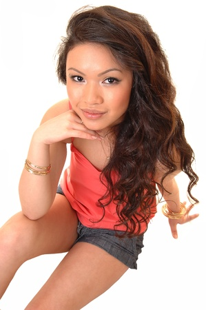A closeup portrait of a young beautiful Asian woman with long curly brunette hair sitting on the floor, for white background. photo