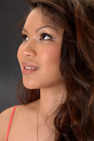 A closeup portrait of a young beautiful Asian woman, looking up, on light gray background.  photo