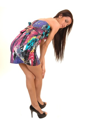 A beautiful young woman in a colorful dress standing in the studio bending down and her long hair shows, for white background. Stock Photo