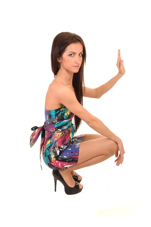 A beautiful young woman in a colorful dress hocking in the studio  holding her hand up, for white background. photo