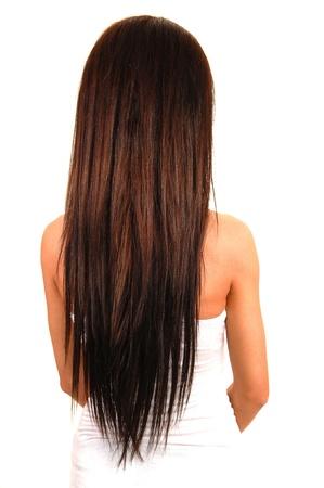 Una hermosa joven en un top blanco permanente en el estudio y mostrando su hermoso cabello Morena, de fondo blanco. Foto de archivo - 9397461