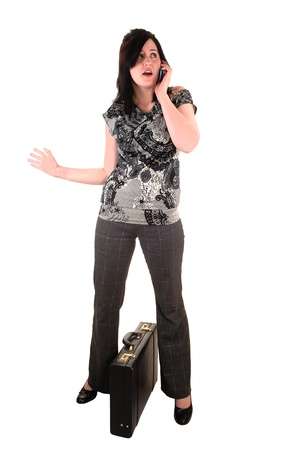 A young business woman with a briefcase and a cell phone in her hand, in slakes and blouse, for white background. Stock Photo - 9418977