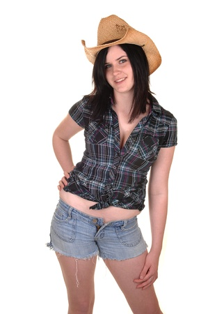 A lovely young woman in a blue blouse and straw cowboy hat standing in shorts in the studio for white background. photo
