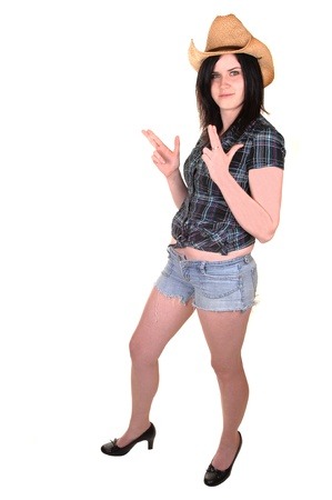 A lovely young woman in a blue blouse and straw cowboy hat standing in jeans shorts in the studio for white background.