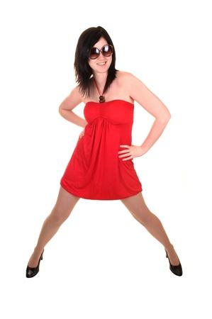 legs spread: Una joven y bella mujer en un vestido rojo y la posici�n de pelo negro con sus piernas se extendi� en el estudio, para el fondo blanco. Foto de archivo