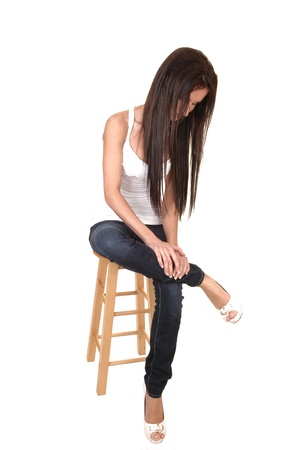 1 person: A young pretty woman in jeans sitting on a chair and her long hair falling down, the studio with her legs crossed, for white background. Stock Photo
