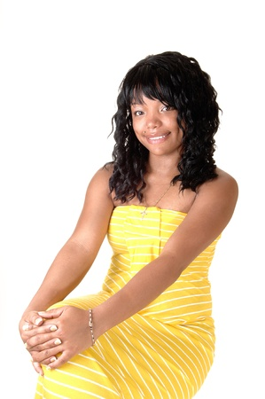 A beautiful African-American woman in a long yellow dress and darkblack hair sitting on a chair, for white background. photo