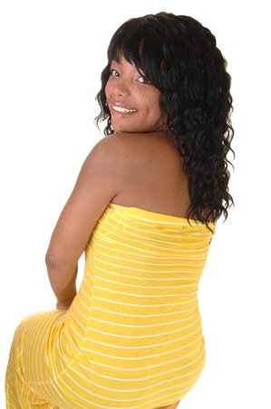 A beautiful African-American woman in a long yellow dress and darkblack hair sitting from the back looking over shoulder, on white background.