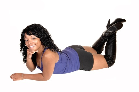 A pretty African American woman in shorts and black boots lying on herstomach on the floor in the studio, for white background.