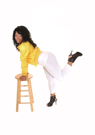 A young pretty African American woman standing in white tights anda yellow jacket, hands on a chair, for white background. photo