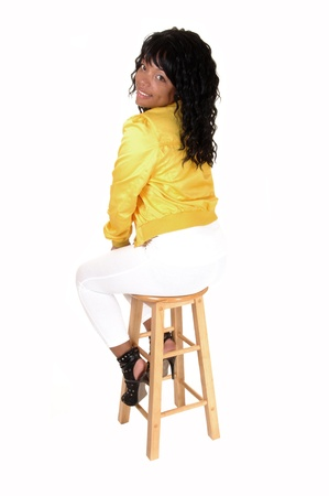 A young pretty African American woman sitting on an chair in white tights and a yellow jacket from the back, looking over her shoulder, for white background. Stock Photo - 9620656