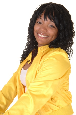 A beautiful African American woman sitting in a yellow jacket andsmiling into the camera, on white background. photo