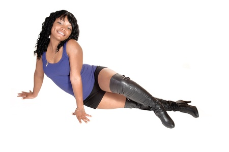 A pretty African American woman in shorts and black boots sitting on the floor in the studio, for white background.