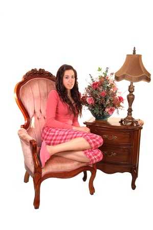 A young pretty woman in pajamas, sitting in a pink armchair with an nightstand and lamp for white background. photo