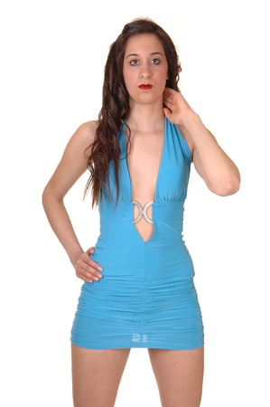 A young pretty woman standing in a short tight blue dress in thestudio, with her long brown hair, for white background. Stock Photo