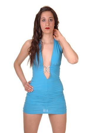 Een jonge mooie vrouw permanent in een korte strak blauwe jurk in thestudio, met haar lang bruin haar, voor witte achtergrond. Stockfoto - 9620686