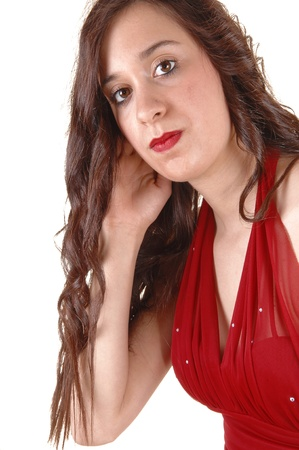 A closeup of a young pretty woman in a red dress in profile standingin the studio for white background. Stock Photo - 9620690