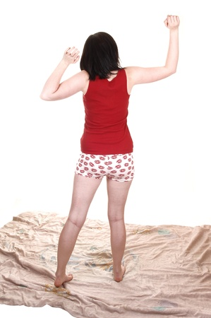 A lovely young woman is stretching after a good night sleep, standingon her comforter in night wear shorts, for white background. photo