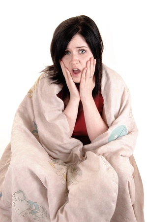 A young girl sitting on the floor covert in a blanket holding her fingerto her mouths and thinking hard, for white background. photo