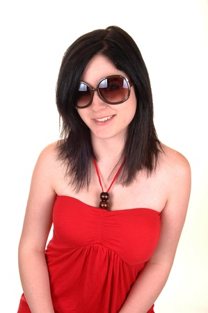 A closeup portrait of a young woman with sunglasses and black hairsmiling into the camera, in a red dress on white background. photo