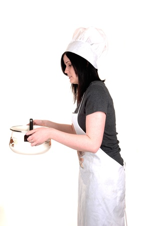 A pretty young woman, holding a cook pot, standing with an apron, black hair and a cook hat for white background. photo