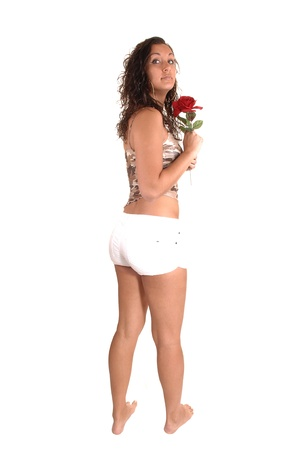 nice butt: A lovely girl standing from the back in the studio, looking over her shouldershowing her nice figure und butt, with a rose in her hand, over white.