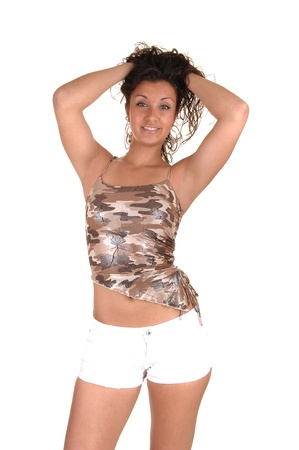 Pretty girl in a beige blouse and white shorts messing with her hairfor white background. photo