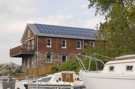 An old house outfitted with modern solar cells on the rooftop to harvestenergy from the sun, with sailboats in the foreground. photo