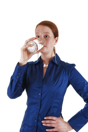 A young healthy woman standing in the studio and drinking a glassof water, for white background. photo