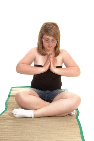 Young teenager sitting on a matt and concentrating on her yoga sessionwith glasses and her eyes closed, for white background. photo