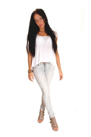A pretty young lady in light gray jeans and long black hair standing inthe studio with her legs grossed, for white background. Reklamní fotografie