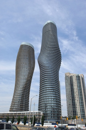 Two modern new high rise building towers in Mississauga in very interestinground forms, the right one is occupied the left one under construction