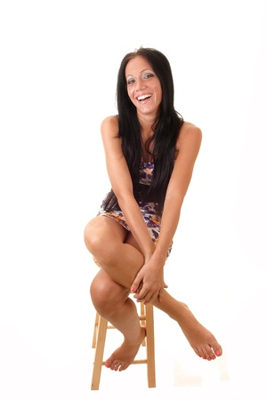 bare body women: A young girl sitting on a chair with her long black hair in a colorfuldress, looking into the camera and laughing, for white background. Stock Photo