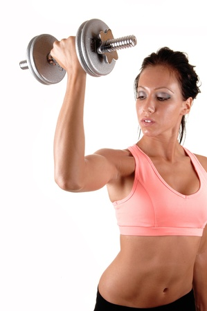 Pretty young woman lifting a dumbbell with her right arm showing hermuscles and very lean body, for white background. photo