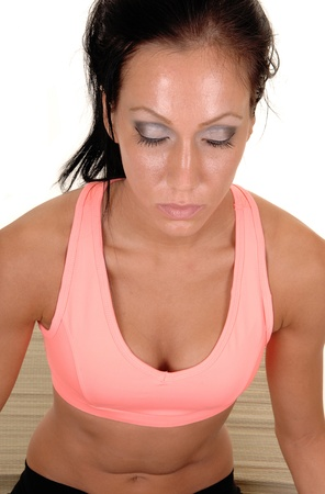 Woman sitting on the floor of a mat, relaxing with yoga with her eyes closed, in close-up, for white background. photo