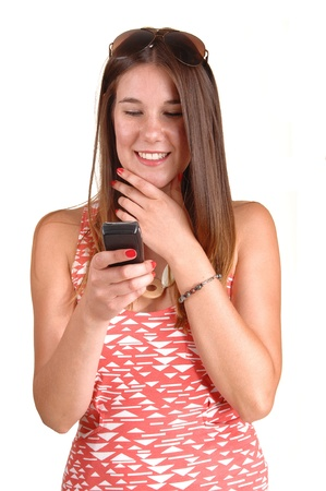 A lovely woman has a good time reading the message on her cellphone, in a pink dress and smiling, over white background. photo