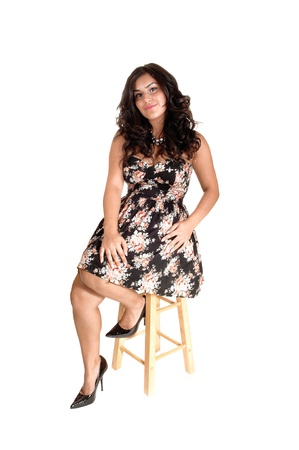 A very pretty teenager in a beautiful dress and long black curly hair, sittingon a chair in high heels for white background. Stock Photo - 10536138