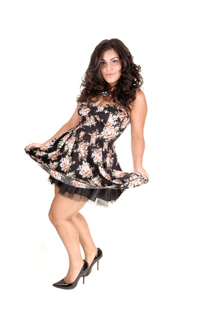 A beautiful girl in a nice dress, with long curly black hair and high heelsstanding in the studio, dancing, for white background. Stock Photo - 10606748