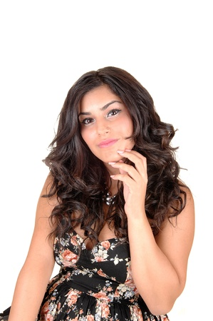 A portrait shot of a very pretty teenage girl with long black curly hairand a black dress with flowers in, for white background. Stock Photo - 10606755